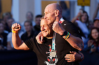 Pictured: Gareth Thomas celebrates with his husband Stephen (L) after crossing the finish line. Sunday 15 September 2019<br /> Re: Ironman triathlon event in Tenby, Wales, UK.