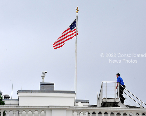 An unidentified White House worker goes to lower the American Flag that flies over the White House to half-staff in Washington, D.C. in remembrance of those killed in Aurora, Colorado on Friday, July 20, 2012..Credit: Ron Sachs / Pool via CNP