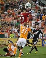 Troy Perkins #23 of D.C. United holds on to the ball above Andrew Hainault #31 of the Houston Dynamo during an MLS match at RFK Stadium in Washington D.C. on September  25 2010. Houston won 3-1.