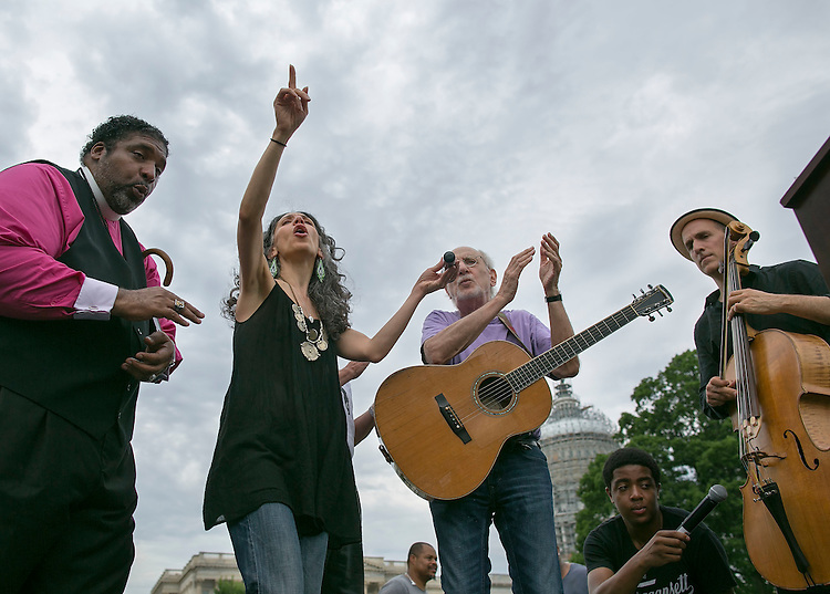 UNITED STATES - JUNE 15 - From left, Rev. William Barber II, President of the North Carolina chapter of the NAACP, Peter Yarrow, Bethany Yarrow, and Rufus Cappadocia, all from New York, sing and dance during a rally by the National Rural Health Association on the Southeast lawn of the U.S. Capitol on Monday, June 15, 2015. Around 20 members of the group marched 283 miles from Belhaven, N.C. to the Capitol, symbolizing one mile for each rural hospital that is at risk of closing. (Photo By Al Drago/CQ Roll Call)