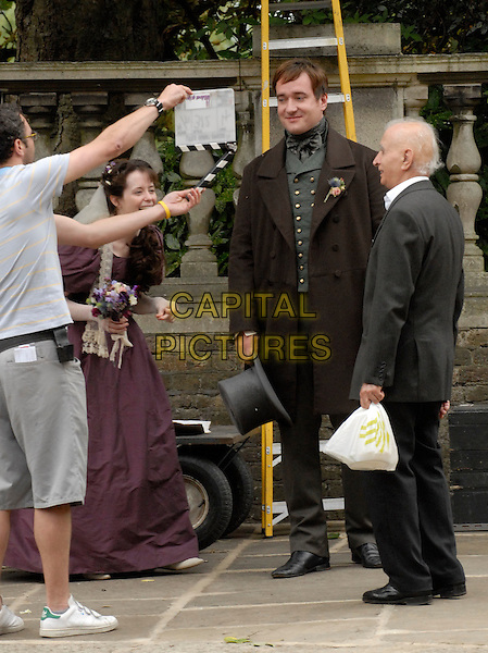 """CLAIRE FOY & MATTHEW MacFADYEN with an elderly man as he mistakenly wanders into the scene.On the set of Charles Dickins serial novel, period drama """"Little Dorrit"""" filming near St. John's Church in Hampstead, London, England, Bank Holiday Monday, August 25th 2008..filmset film set Full length costume Victorian funny clapperboard laughing .CAP/IA.©Ian Allis/Capital Pictures"""