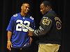 New York Giants running back Rashad Jennings, left, presents Roosevelt High School senior Chukwuma Ukwu with the Heart of a Giant Award during a surprise ceremony for Ukwu in the school's auditorium on Tuesday, Dec. 15, 2015. Ukwu, who played on Roosevelt's varsity football team, was honored for his dedication on the gridiron and exceptional service to his local community.