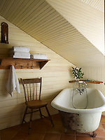 The walls and ceiling of this attic bathroom have been clad in tongue-and-groove