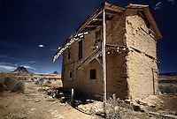 A two storey adobe ruin in the ghost town of Guadalupe, New Mexico with Cerro Santa Clara and Cabezon Peak on the horizon.