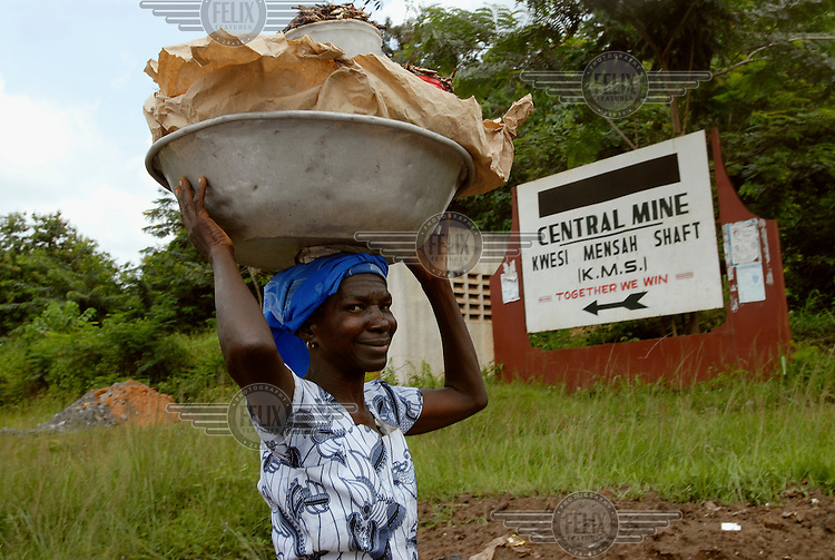 A village woman passes the entrance to the K.M.S. gold mine near Anyinam.