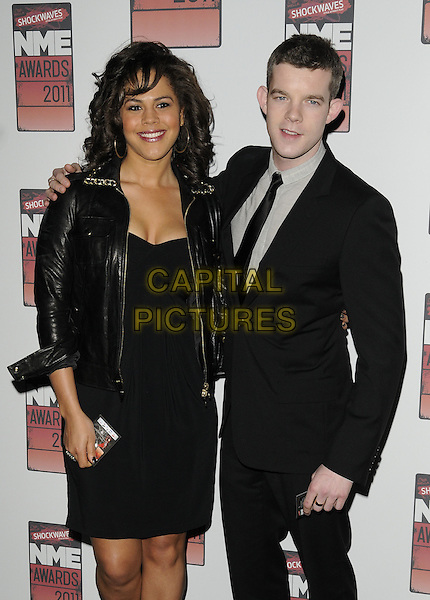 LENORA CRICHLOW & RUSSELL TOVEY.The Shockwaves NME Awards 2011 held at the O2 Academy Brixton - Arrivals London, England, UK,.23rd February 2011..half length black suit grey gray shirt tie dress leather jacket cleavage.CAP/CAN.©Can Nguyen/Capital Pictures.