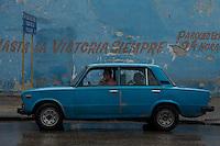 blue russian lada car in front of blue wall with revolutionary graffiti in Havana, Cuba