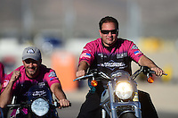 Oct. 27, 2012; Las Vegas, NV, USA: NHRA pro stock motorcycle rider Eddie Krawiec (left) being pushed by Matt Hines during qualifying for the Big O Tires Nationals at The Strip in Las Vegas. Mandatory Credit: Mark J. Rebilas-
