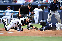 Asheville Tourists catcher Brian Serven (25) tags out a hard sliding Brandon Wagner (33) as home plate umpire Forrest Ladd prepares to make a call during a game against the Charleston RiverDogs at McCormick Field on July 4, 2017 in Asheville, North Carolina. The Tourists defeated the RiverDogs 2-1. (Tony Farlow/Four Seam Images)