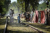 Refugees from Swat valley walk beside makeshift tents next to a railway line. Only a small part of the stream of refugees have been placed in camps. The Pakistani government began an offensive against the Taliban in the Swat Valley in April 2009, which led to a major humanitarian crisis. Up to two million civilians were estimated to have been displaced by the fighting.