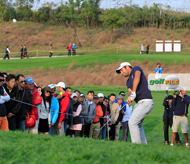 Alexander Levy (FRA) chips into the 16th green from the crowd during Sunday's Final Round of the 2014 BMW Masters held at Lake Malaren, Shanghai, China. 2nd November 2014.<br /> Picture: Eoin Clarke www.golffile.ie