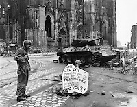 Cologne, Germany - Cpl. Luther E. Boger, Concord, N.C., skytrooper, reads a warning sign in the street. This street leads to the Rhine River and is under observation of the Germans who occupy a stronghold there. Cpl. Boger is with the 82nd Airborne Division. 4 April 1945. The German tank is burnt out and the torsion-bars have been destroyed by the immense heat of the fire.<br /> <br /> <br /> Allied troops captured the western part of Cologne on 6th-7th March 1945. The German army still held the eastern shore of the Rhine and attacked the Allies with artillery. The rest of Cologne was captured between 12th and 15th April 1945. Until the 16th April a strip of about 500m along the shore had been declared as a restricted area and the cathedral was just within this zone.