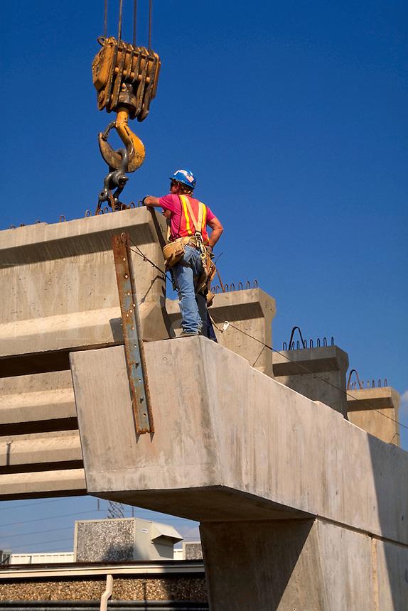 A worker assists a crane operator place concrete beams at a bridge construction site. Construction worker.