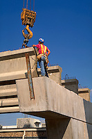 A worker assists a crane operator place concrete beams at a bridge construction site. Construction worker.