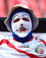 A Costa Rica fan wearing a mask cheers his side on