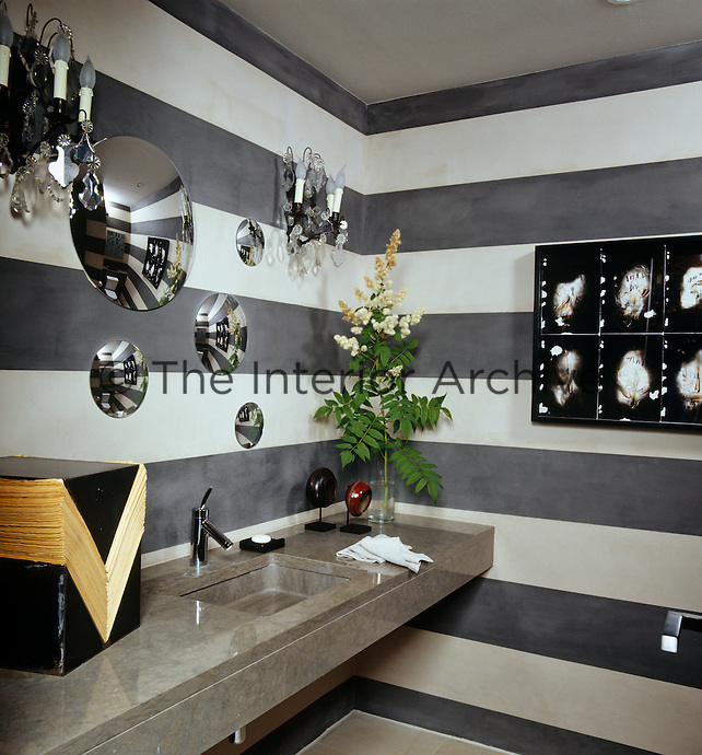 The loo is painted in horizontal black and white stripes punctuated with plastic convex mirrors