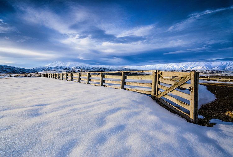 Snow covered stock yards on St Bathans Downs Road, in Winter with the Hawkdun Ranges, Central Otago, South Island, New Zealand - stock photo, canvas, fine art print