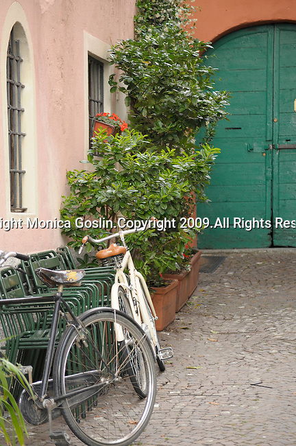 Bikes near a pale pink building, bushes, and a green door in Gravedona, a town on Lake Como, Italy.