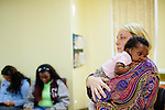 Laura Grumbling, who is in charge of client operations, holds Selea Moore, 2 months, during a class at the Pregnancy Aid Clinic in Hapeville, Georgia as the baby's mother Sequoia Tonge (not pictured), 23, sits nearby. The clinic offers women free support, including ultrasounds, pregnancy tests, classes, and supplies. Seen November 7, 2013. Sequoia first found out she was pregnant at the clinic.
