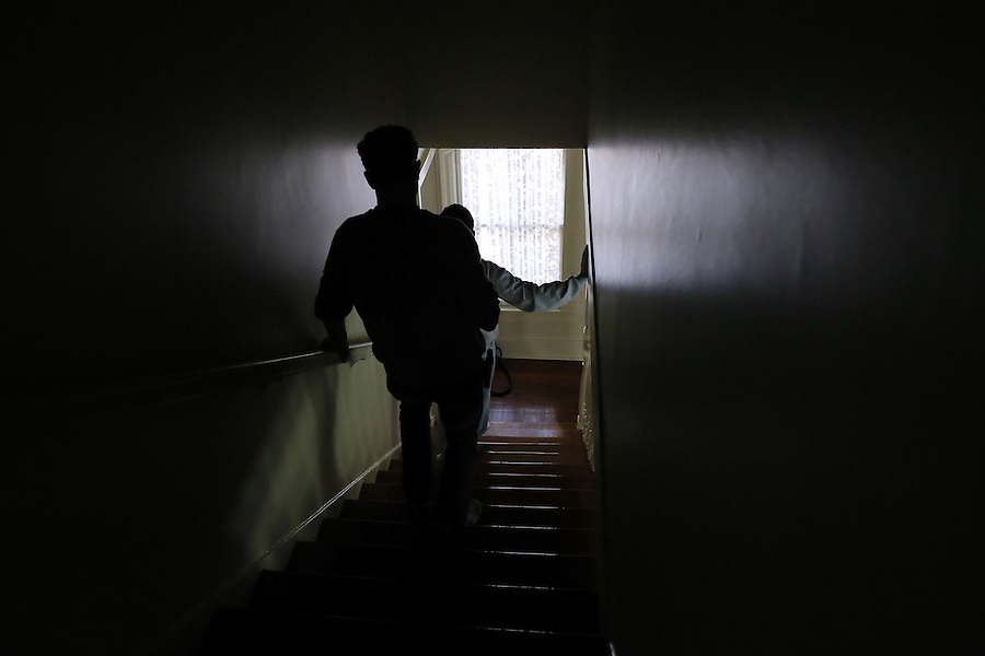 """PLEASE HOLD FOR MARTHA IRVINE STORY: In this Wednesday, March 2, 2016 photo, Sam Alexander, left, assists his son, Ben, down a flight of stairs at their home in Metairie, La. Alexander, 22, has nonverbal autism, a condition that became apparent when he was 2 years old. He has found his voice through writing using what is known as """"facilitated communication,"""" a method in which another person steadies the hand of the autistic person, so he or she can communicate through typing. (AP Photo/Jonathan Bachman)"""