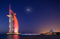 Burj al Arab Hotel, architects W. S. Atkins,  an icon of Dubai built in the shape of the sail of a dhow, stands on an artificial island just off Jumeirah Beach. Jumeirah Beach Hotel in background. Evening.  Dubai. United Arab Emirates.