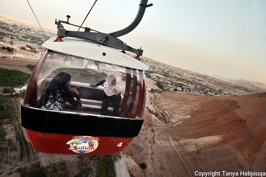 """Young women enjoy a ride up the cable car to the biblical """"Mount of Temptation""""  in the West Bank town of Jericho."""