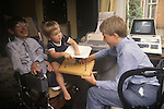 Stephen Hawking and young son Tim on his lap playing with a Black Hole with his elder brother Robert. Hawking family home 1980s UK Cambridge.