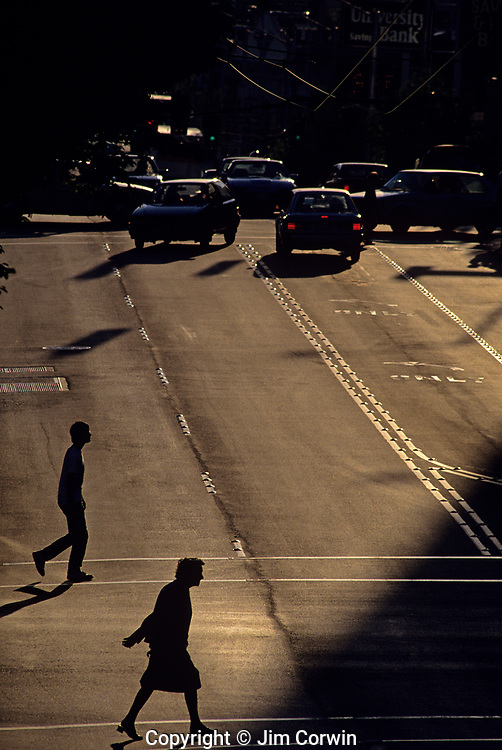 """Silhouetted youth and older woman crossing street toward sunset along """"The Ave"""" in the University District Seattle, Washington State USA"""
