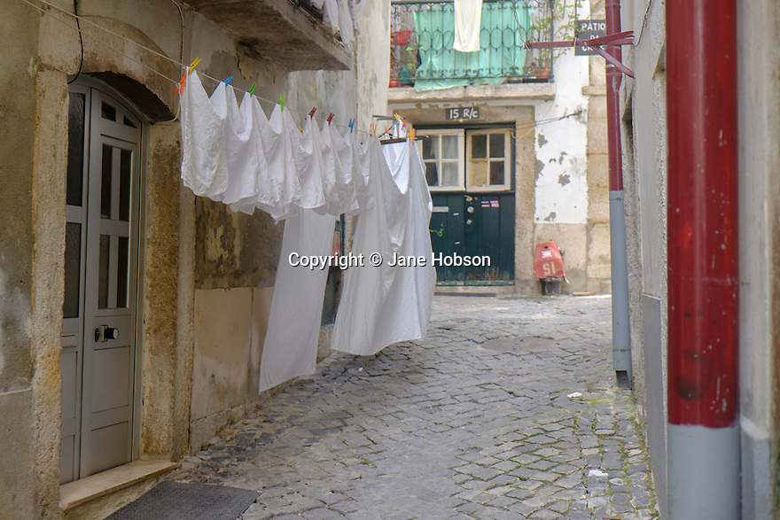 Lisbon, Portugal. 21.03.2015. A typical narrow street, with washing hanging out to dry, in the Alfama district of Lisbon. © Jane Hobson.