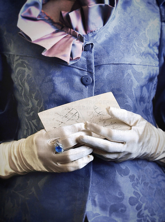 A close-up of female hands in a victorian outfit and white gloves, with a huge ring with a blue rhinestone, holding a vintage poscard/ a letter.