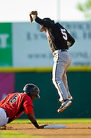 Kannapolis Intimidators shortstop Michael Johnson (5) leaps for a high pick-off throw as Jordan Akins (5) of the Hickory Crawdads dives back into second base at L.P. Frans Stadium on May 25, 2013 in Hickory, North Carolina.  The Crawdads defeated the Intimidators 14-3.  (Brian Westerholt/Four Seam Images)