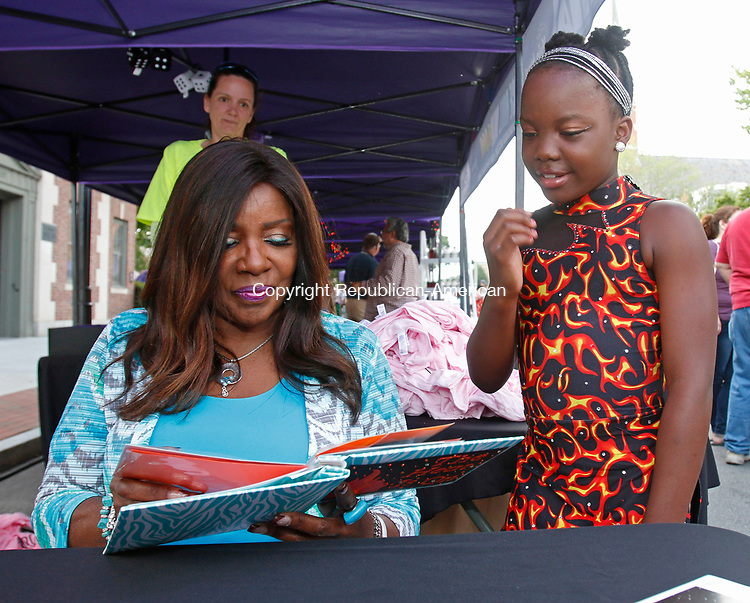 Torrington, CT- July 072717MK02 Gloria Gaynor looks at a scrap book that Emily Lapointe gave to her at the Main Street Marketplace in Torrington Thursday evening. The book depicted  how Lapointe danced to Gaynor's music during multiple championships as well as a recent national competition.  Gloria Gaynor greeted dozens of fans and took photos with them along with signing autographs at the event.  Michael Kabelka / Republican-American
