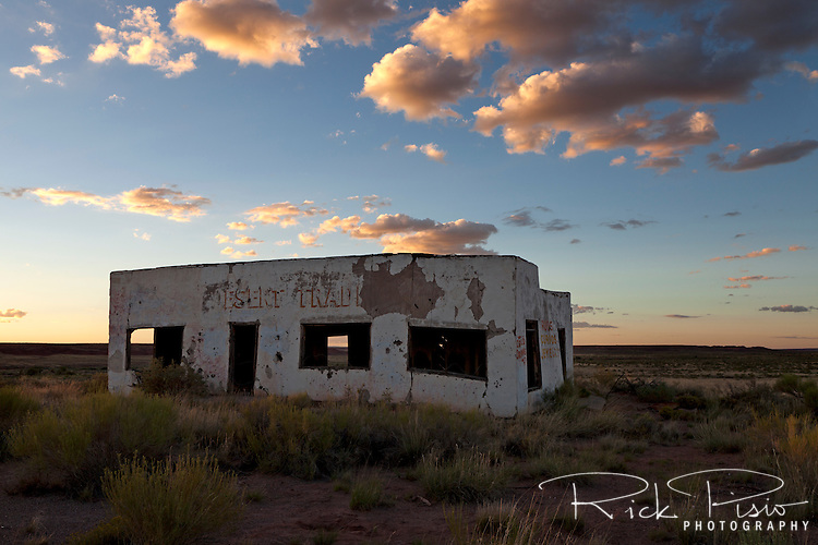 The abandoned Painted Desert Trading Post along a bypassed section of Route 66 in Arizona at sunset.