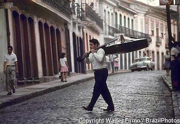 Man carries musical instrument by the streets of Ouro Preto, State: Minas Gerais, Brazil. World Cultural Heritage.
