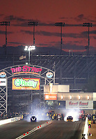 Nov 2, 2019; Las Vegas, NV, USA; The sun sets behind the track as NHRA top alcohol funny car drivers do burnouts during the Dodge Nationals at The Strip at Las Vegas Motor Speedway. Mandatory Credit: Mark J. Rebilas-USA TODAY Sports