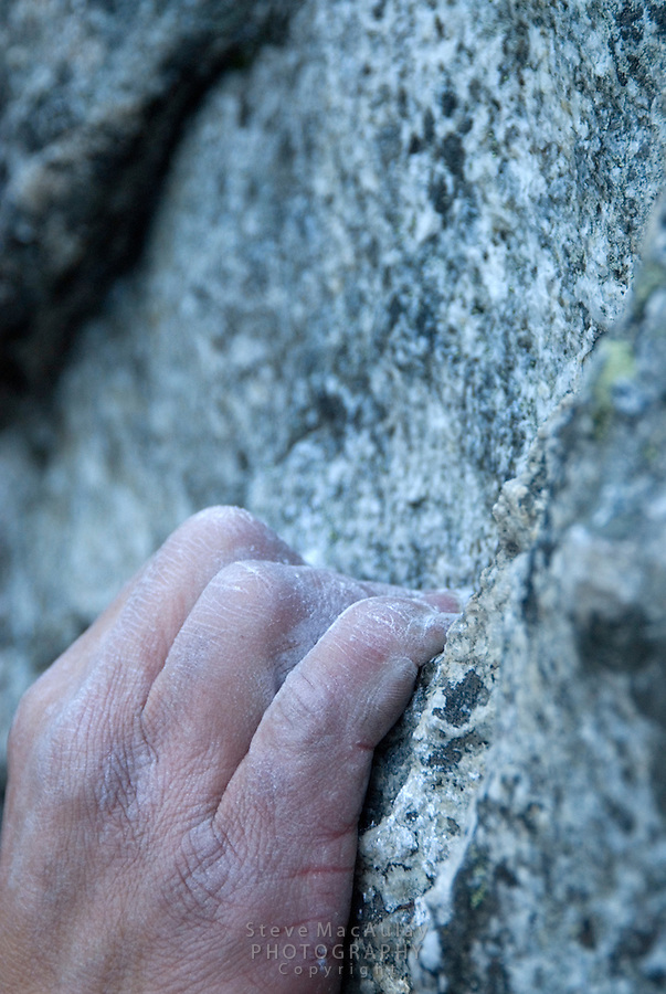 Close-up shot of rock climbers hand gripping hold on granite cliff, Grand Teton National Park, Wyoming