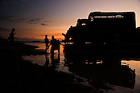 Ferry crossing the Manambolo river with a truck at dusk in silhouette