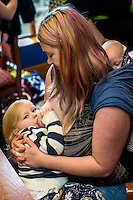 A mother breastfeeds her two year old daughter with her twelve week old baby asleep in a sling on her back.in the family restaurant and play area of a pub.<br /> <br /> Lancashire, England, UK<br /> <br /> Date Taken:<br /> 07-01-2015<br /> <br /> &copy; Paul Carter / wdiip.co.uk