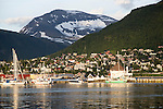 Suburban housing and landscape of snow on mountain side, Tromso, Norway warm evening light