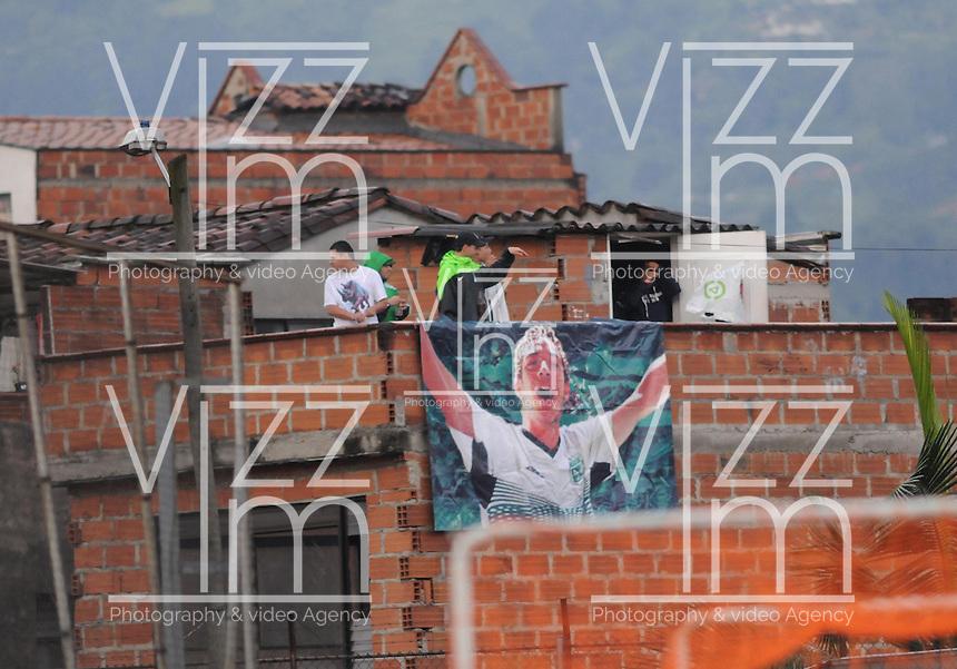 MEDELLIN -COLOMBIA-26-04-2014: Hinchas del Atletico Nacional observan el partido desde los techos de las casas contiguas al estadio Polideportivo  sur entre el Envigado F.C y el Atletico Nacional durante  de los cuartos de final  de la Liga Postobon I 2014, jugado en el estadio Polideportivo Sur  de Medellin. / Atletico Nacional fans watch the game from the roofs of the adjoining houses to the Polideportrivo Sur stadium between Envigado FC and Atletico Nacional during the quarterfinals of the League I Postobon 2014, played at the Sports Stadium Southern Medellin. Photo: VizzorImage  / Luis Rios  / Str.