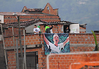 MEDELLIN -COLOMBIA-26-04-2014: Hinchas del Atletico Nacional observan el partido desde los techos de las casas contiguas al estadio Polideportivo  sur entre el Envigado F.C y el Atletico Nacional durante  de los cuartos de final  de la Liga Postobon I 2014, jugado en el estadio Polideportivo Sur  de Medellin. / Atletico Nacional fans watch the game from the roofs of the adjoining houses to the Polideportrivo Sur stadium between Envigado FC and Atletico Nacional during the quarterfinals of the League I Postobon 2014, played at the Sports Stadium Southern Medellin. Photo: VizzorImage  / Luis Rios  / Str.