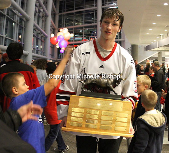 UNO's Zahn Raubenheimer walks the Spirit of the Maverick trophy through the lobby of the Qwest Center during post-game celebrations Saturday night. (Photo by Michelle Bishop)