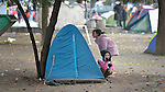 Afghan refugee girls play hide and seek behind a tent in a city park in Belgrade, Serbia. The park has filled with refugees from several countries stopping over on their way to Germany, Sweden, Holland, and elsewhere. <br /> <br /> Parental consent obtained.