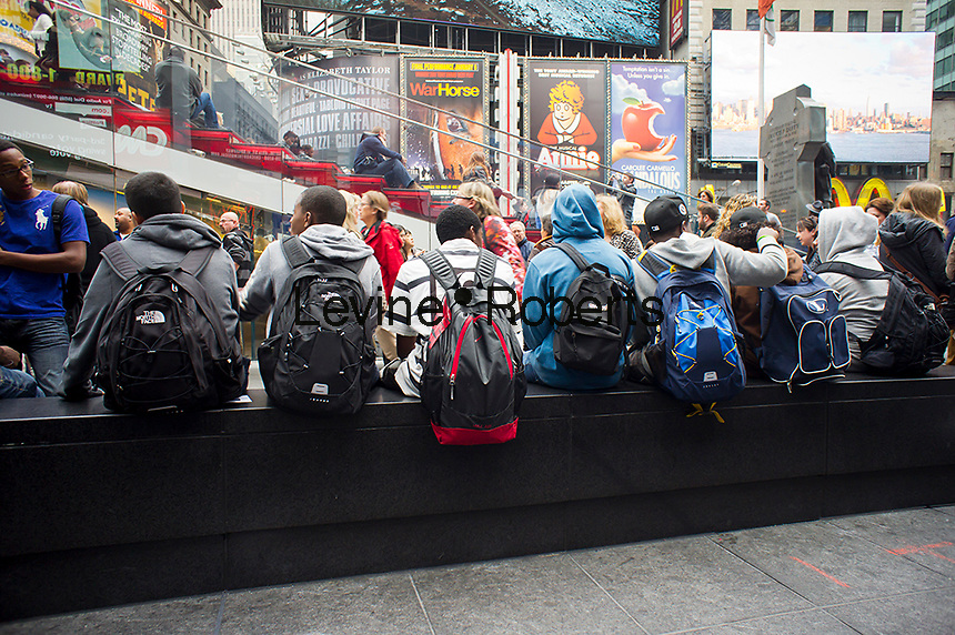 Students wearing backpacks laden with books hang out in Times Square in new York after school on Friday, October 26, 2012.  (© Richard B. Levine)