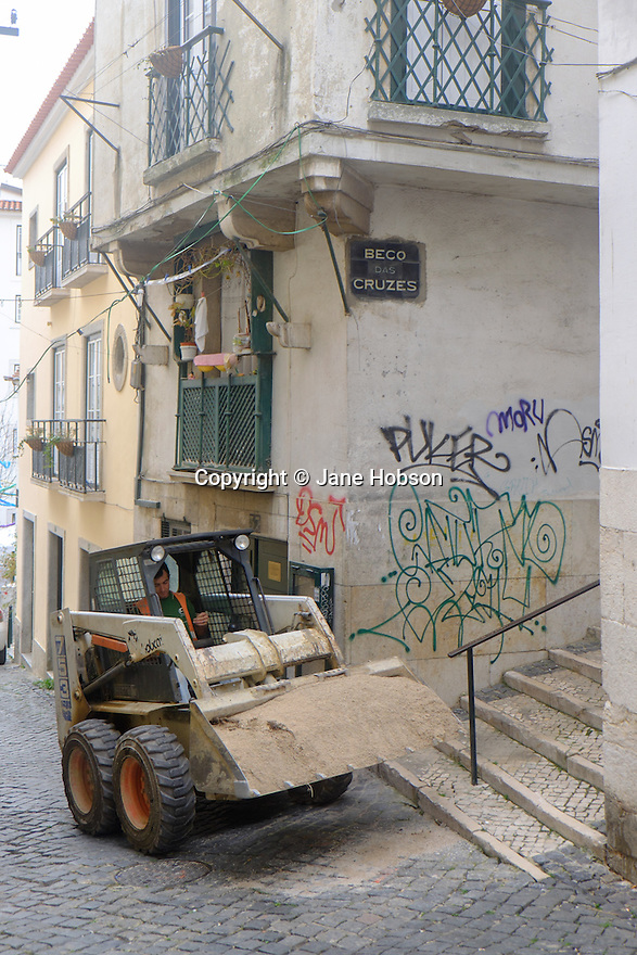 Lisbon, Portugal. 21.03.2015. A bulldozer in a typical narrow street in the Alfama district of Lisbon. The process of gentrification continues in this ancient part of the city. Still inhabited by older residents, in rent-controlled apartments, they are gradually being replaced by wealthier owners wanting renovated homes, or for the holiday and buy-to-let maket. © Jane Hobson.