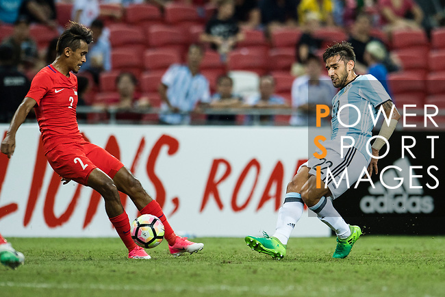 Shakir Hamza of Singapore (L) and Eduardo Salvio of Argentina (R) who looks to bring the ball down during the International Test match between Argentina and Singapore at National Stadium on June 13, 2017 in Singapore. Photo by Marcio Rodrigo Machado / Power Sport Images
