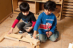 Education preschool 3-4 year olds block area two boys playing with wooden blocks and human figures horizontal playing together
