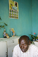 Rwanda. Southern province. Mataba village. Pierre Claver Karenzi is hutu, seated on a bench at home. Religious posters on the wall, with representations of Jesus Christ, the Virgin Mary and a catholic Holy cross.  © 2007 Didier Ruef