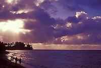 People walking on beach at sunset on Waialua Beach, near Haleiwa, North Shore of Oahu