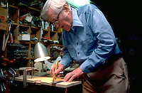 Retired physician age 85 marking board for cutting in his workshop.  Minneapolis  Minnesota USA